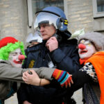 Climate change demonstrators dressed as clowns hug a police officer outside the Danish Foreign Ministry while demonstrators pass during the climate march in Copenhagen on December 12, 2009. At least 30,000 people marched through Copenhagen, demanding world leaders declare war on the greenhouse gases that threaten future generations with hunger, poverty and homelessness. If all goes well, the 194-nation conference under the UN's Framework Convention on Climate Change (UNFCCC) will wrap up on December 18 with a historic deal sealed by more than 110 heads of state and government. TOPSHOTS/ AFP PHOTO/ ADRIAN DENNIS (Photo credit should read ADRIAN DENNIS/ AFP/ Getty Images)